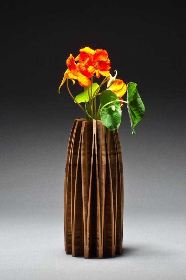 Bamboo vase cut from one piece of wood and opened up to create a beautiful form, with glass vial inside for water and flowers