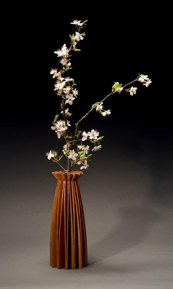 Poppy vase of cherry wood, one piece of wood, cut and opened up to create a graceful form. With glass tube for water and flowers