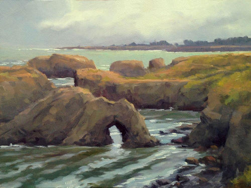 Mendocino Headlands with arch rock under cloud cover, yellow green grass above and shades of green ocean.