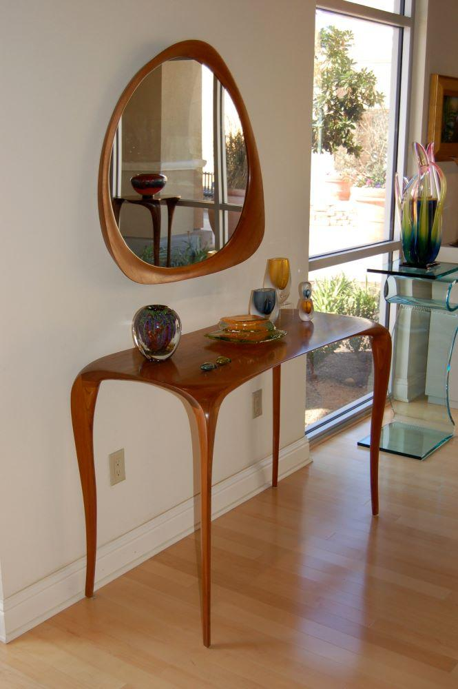 carved console table and free-form mirror