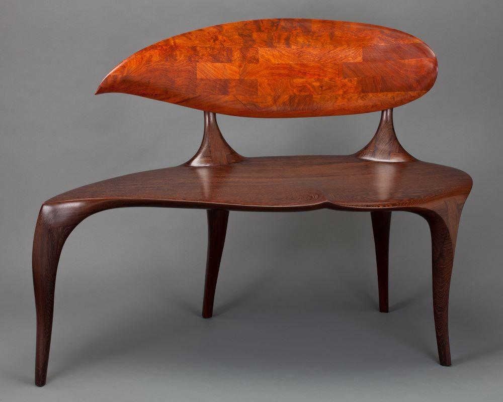 teardrop shaped back and seat of carved wenge and African mahogany bench