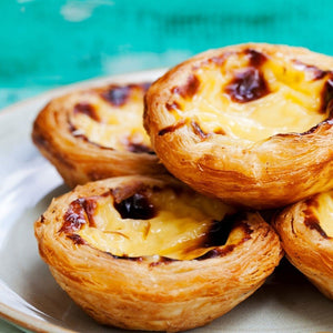 "No ""visit to Portugal"" is complete without a crispy bite of the classic Pastel de Nata (Portuguese Custard Tarts)."