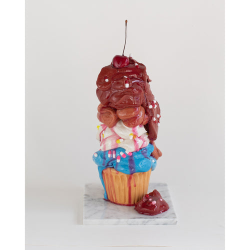Sculpture of a cupcake by Olivia Bonilla. Marble base with cement and resin accents in the shape of a gooey cupcake with a cherry on top.