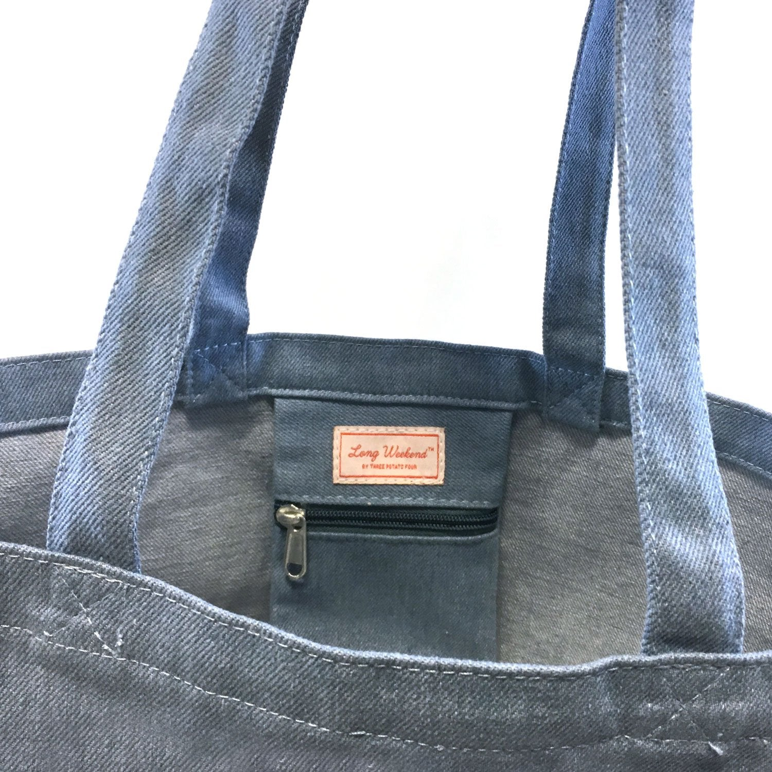 interior zip pocket of soft washed denim tote bag with white graphic sun design