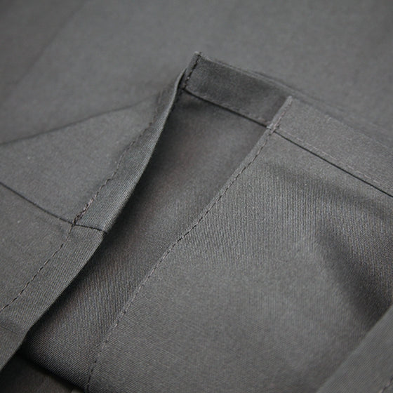 Close-up of the bottom hem and inner-stitching on the pleats.