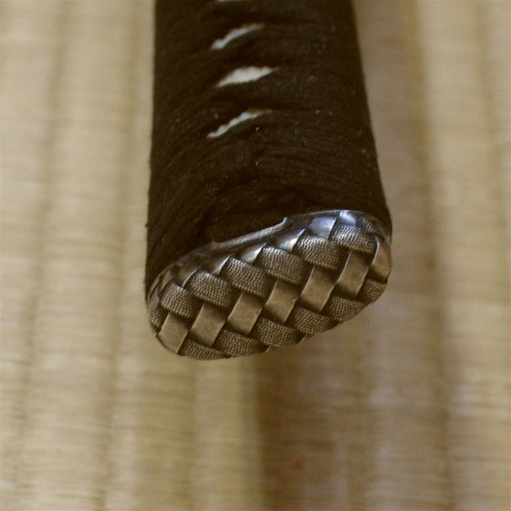 The tsuka kashira featuring silver-plated kago style fittings.