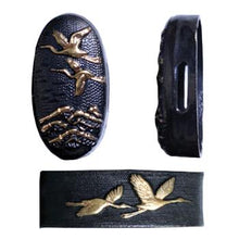 The blackened brass fuchi and kashira showing a tortoise and crane.