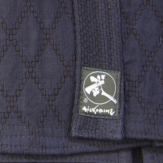 View of the double-layered dogi's hishi-zashi stiching at the bottom alongside the Tozando label.