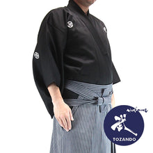 The deluxe polyester dogi with striped hakama seen from the size with Tozando logo.