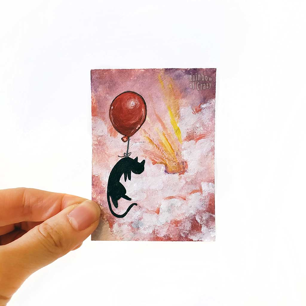 A hand holding an original ACEO painting of a black cat with a red balloon, floating  through the clouds in the sky, painted with reds and purples.