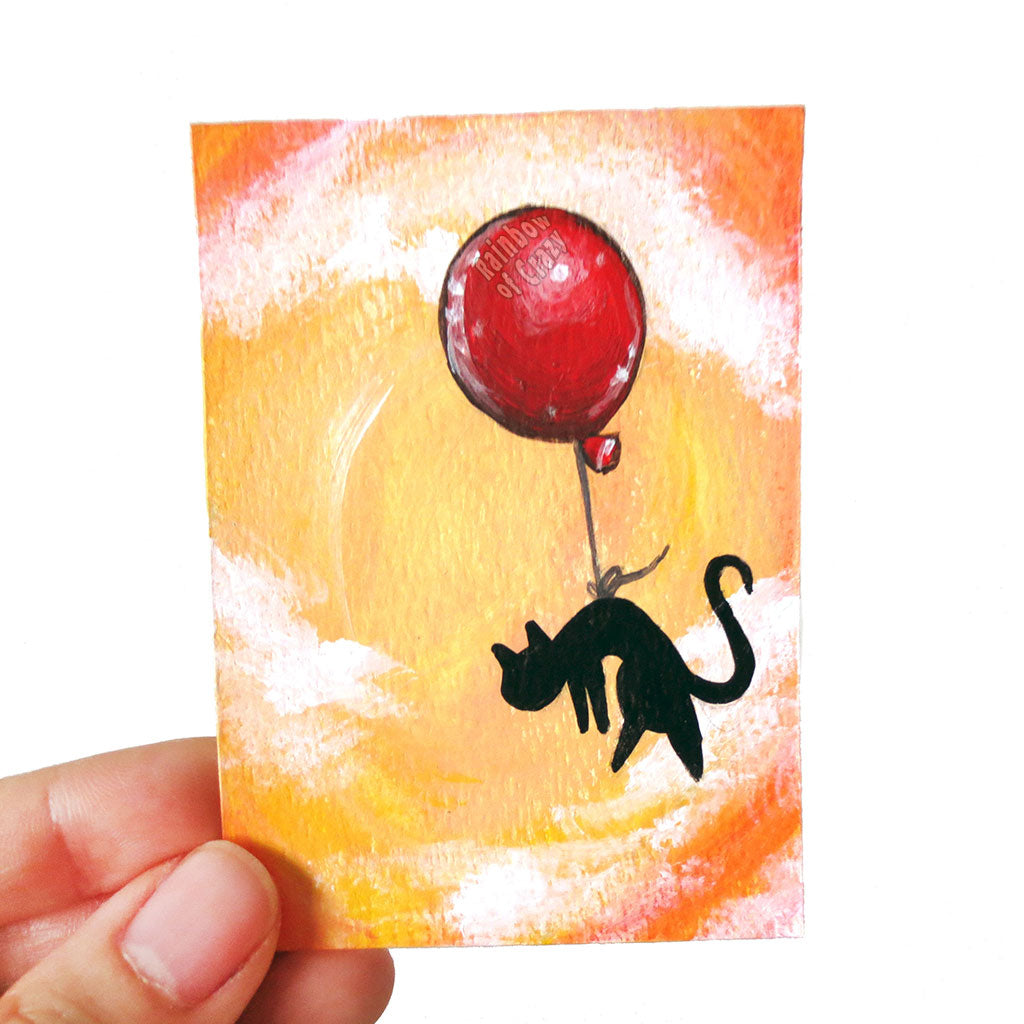 A hand holding a small ACEO size painting of a black cat hanging from a red balloon, floating through a cloudy orange sky.