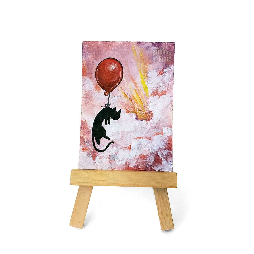 An original ACEO painting, on an easel, of a black cat with a red balloon, floating  through the clouds in the sky, painted with reds and purples.