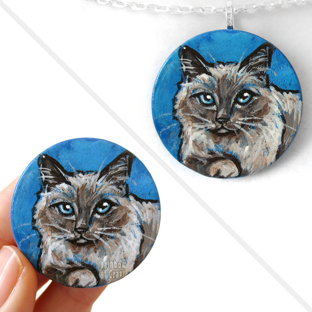 A circle wooden disc, with cat art of a Birman cat with blue eyes, with a blue background. Available as either a wood keepsake or pendant necklace