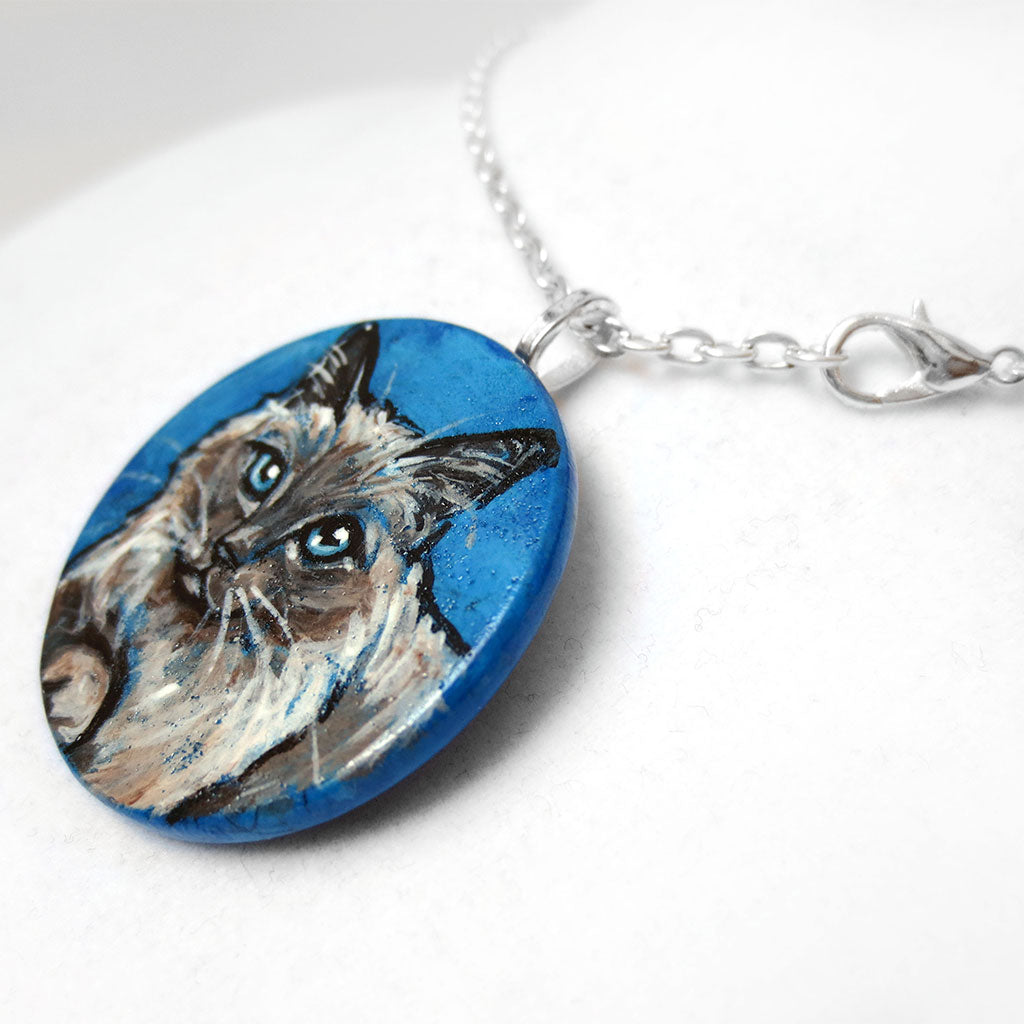 a wooden pendant necklace painted with a portrait of a birman cat with blue eyes, on a blue background