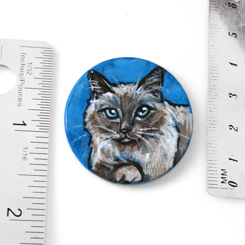 a circle shaped wooden disc, hand painted with a brown and white birman cat with blue eyes. the piece is next to two rulers to show its size: 1 1/2 inches or 3.8 cm across