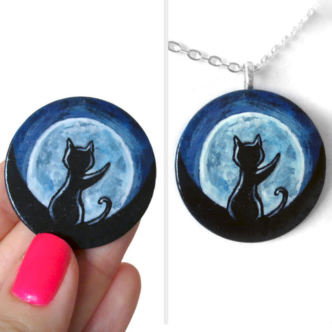 A lightweight wooden disc features art of the silhouette of a black cat, with a front paw reaching up, sitting in front of a big glowing full moon. Available as a keepsake or necklace