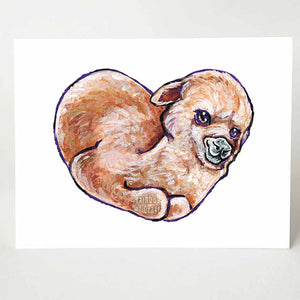 A greeting card with art of a brown alpaca on the front, curled up on the shape of a heart.