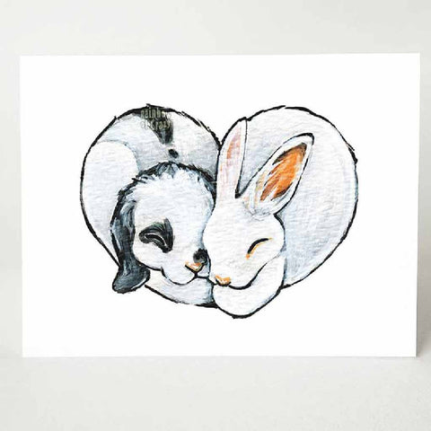 A greeting card, printed with art of two rabbits (a white and black mini lop, and a white Polish), cuddled together in the shape of a heart.