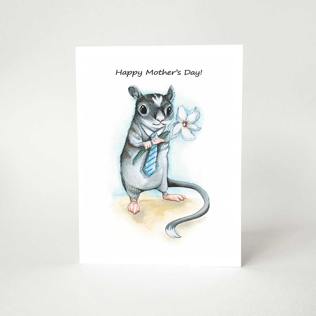 "A greeting card printed wtih art of a gerbil, wearing a blue tie and holding a flower, it reads, ""Happy Mother's Day!"""