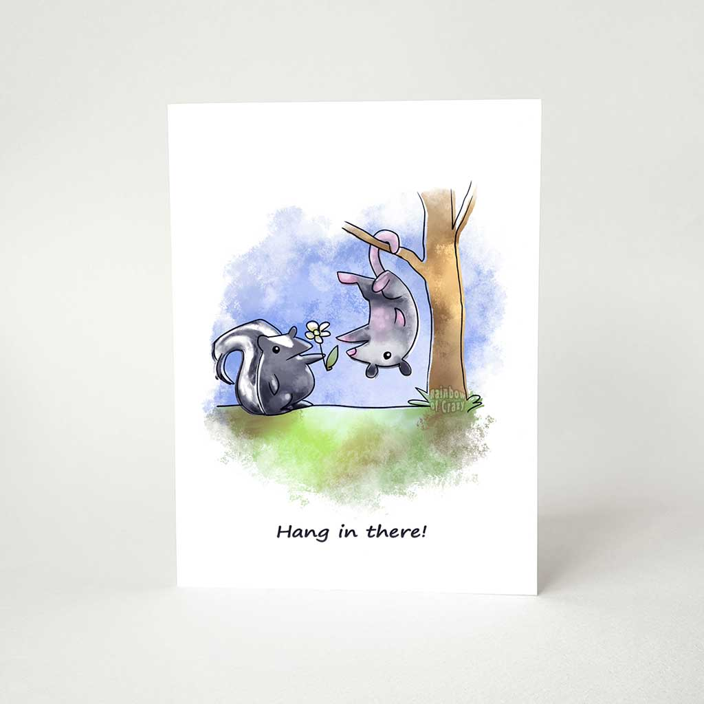 "a greeting card printed with an illustration of a skunk holding out a flower towards a possum hanging upside down, with the text, ""Hang in there!"""