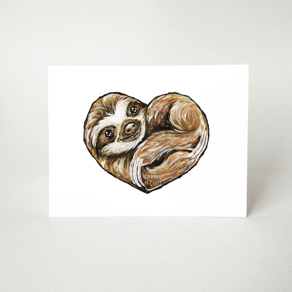 A greeting card featuring art of a smiling sloth, curled up in the shape of a heart.