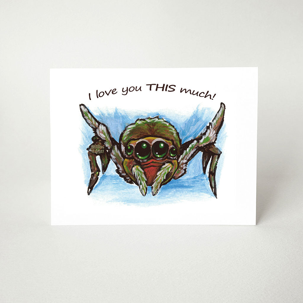 "A greeting card printed with art of a brown and red baby spider, with its two front legs stretched out, the card reads, ""I loveyou THIS much!"""