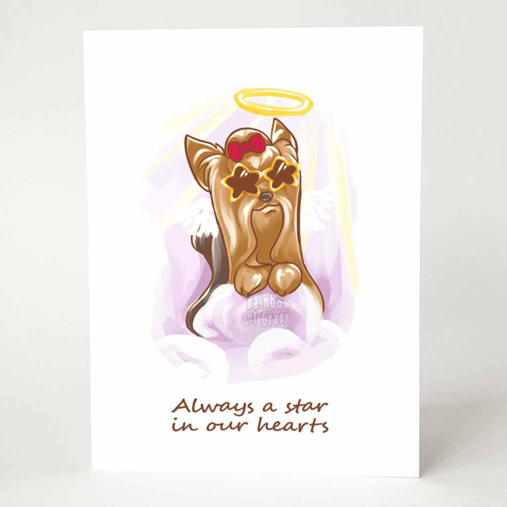 "A greeting card with an illustration of a Yorkshire Terrier as an angel, wearing star shaped sunglasses and a red bow on its head, it sits on purple clouds. The card reads, ""Always a star in our hearts"""
