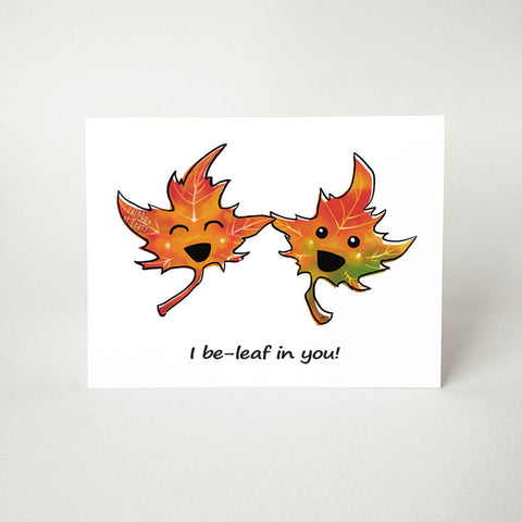 "A greeting card with a graphic of two cartoon maple leaves with eyes and smiles, the card reads, ""I be-leaf in you!"", a pun on the word ""believe"""