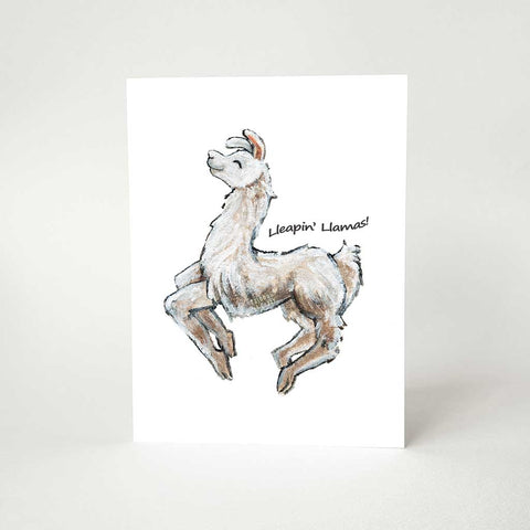 "A greeting card, printed with an illustration of a smiling white and brown llama jumping, with the words ""Lleapin' Llamas!"""