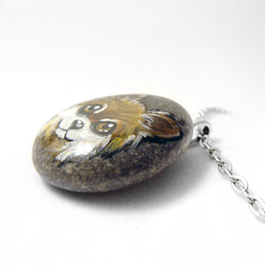 a pendant necklace handmade from a beach rock, hand painted with a dog portrait of a brown and white chihuahua