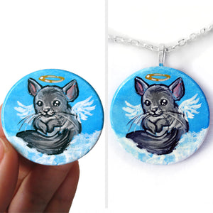 a smooth wood disc features pet art: a chinchilla painted as an angel in the clouds. this portrait is available as a keepsake or a pendant necklace