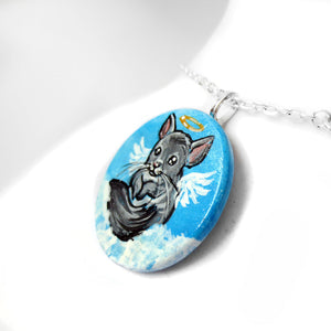 available as a necklace, a wooden pendant is hand painted with a portrait of a chinchilla as an angel in the cloudy sky