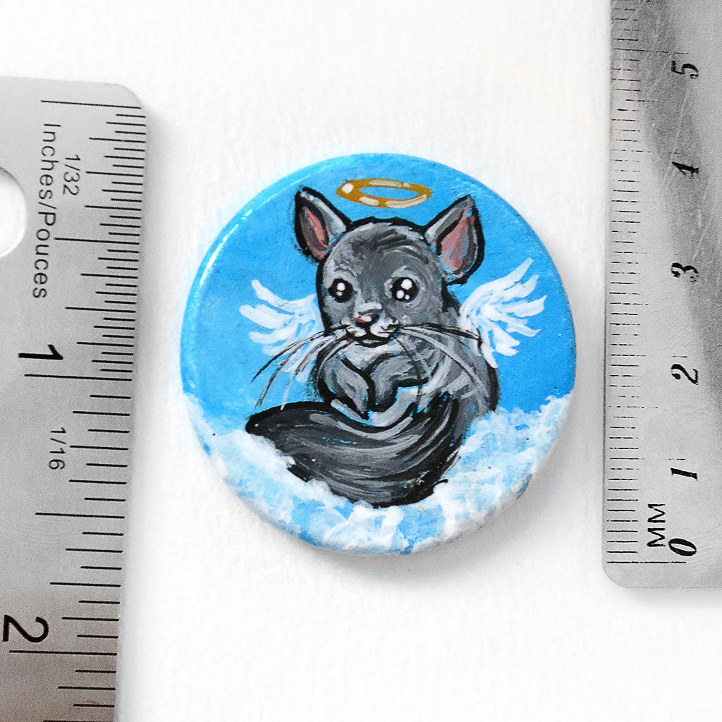 the chinchilla angel painting, next to two rulers to show its size: 1 1/2 inches or 3.8 cm across