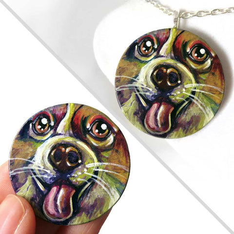 A circle wood pendant featuring a portrait of a corgi in all the colours of the rainbow. Available as either a keepsake or a necklace