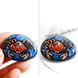 a small beach rock, hand painted with zodiac art: an orange and red crab, the sign of cancer, surrounded by blue water. available as a stone keepsake or pendant necklace