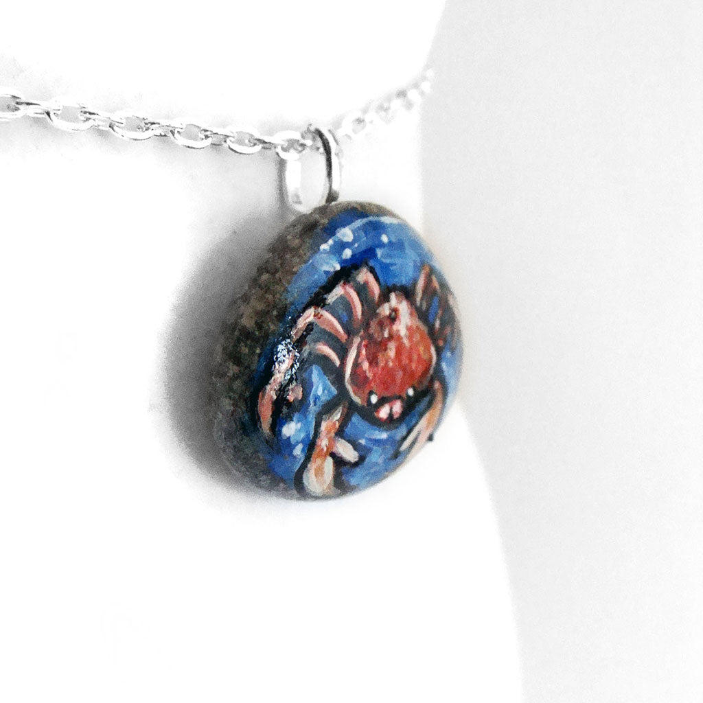 a stone necklace, hand painted with a crab, the zodiac sign of cancer, surrounded by blue water