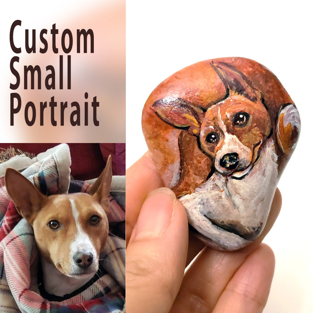 a small beach rock custom painted with a portrait of a Basenji dog