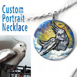 A custom pet portrait painting, on a circle wood necklace, of a grey cockatiel bird as an angel, sitting on clouds