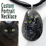 a small beach rock crafted into a custom portrait necklace, with art of a black cat with yellow and green eyes