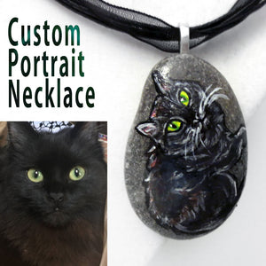 A custom made pendant necklace, featuring a pet portrait painting of a black cat with yellow eyes