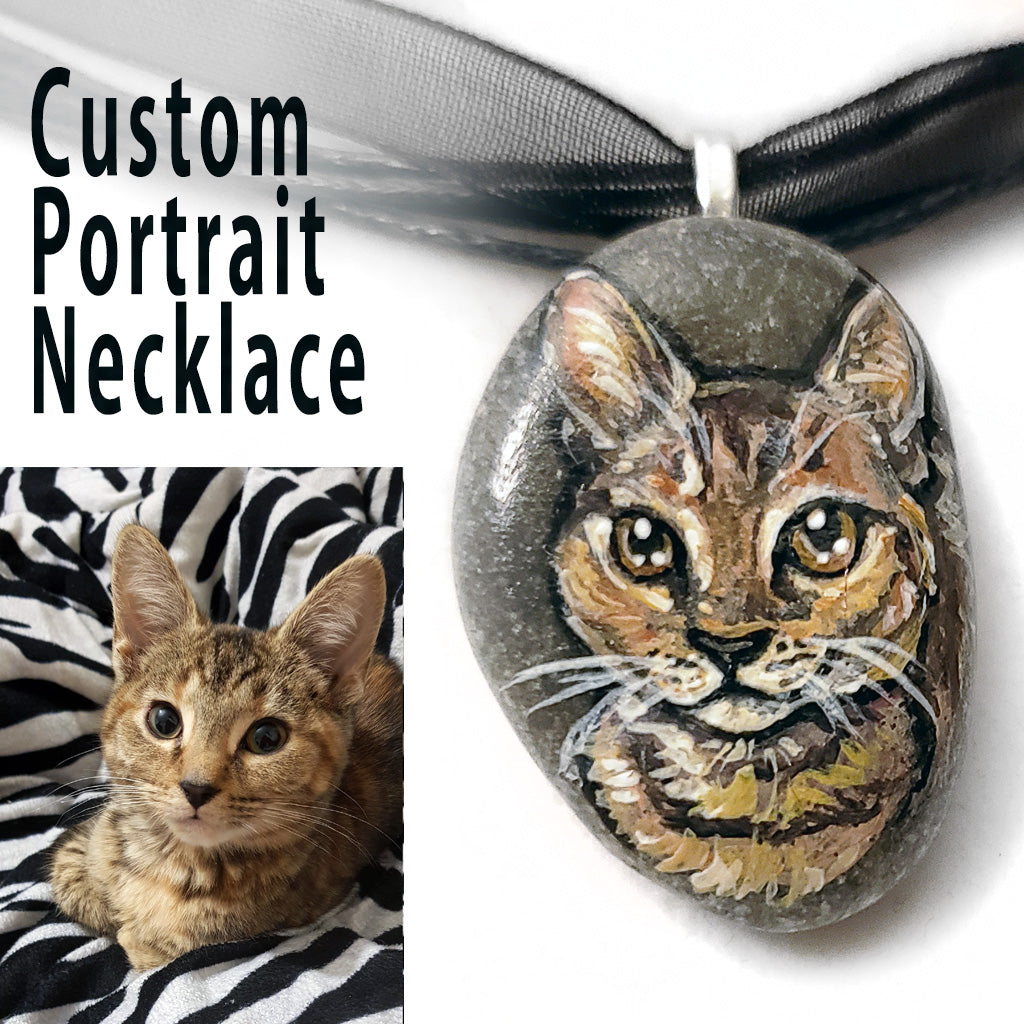a small beach stone, hand painted with the portrait of a brown tabby cat, and made into a pendant necklace