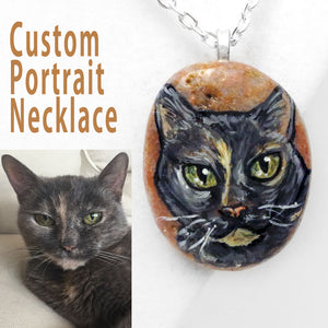 A small beach stone is handpainted with a portrait of a grey cat and crafted into a necklace.