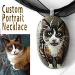 A personalized pet necklace, made from a beach stone, includes a portrait painting of a snowshoe cat