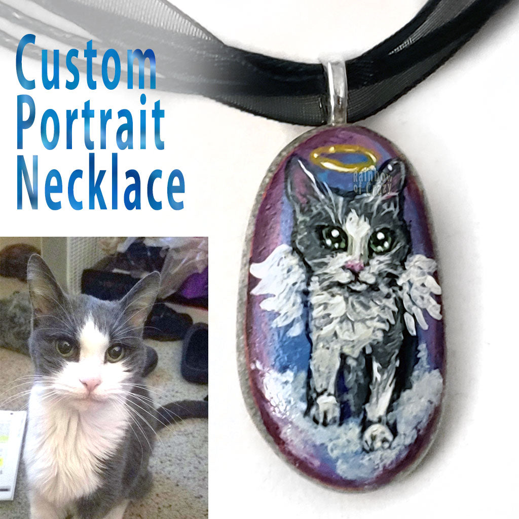 A pendant necklace made from a small beach pebble, hand painted with a custom pet portrait of a grey and white cat as an angel.