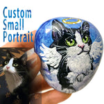 a small stone hand painted with a custom pet portrait of a black and white cat as an angel on the clouds