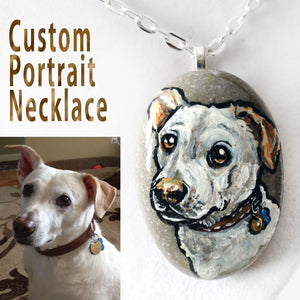 A beach stone is hand painted and crafted into a necklace, customized with a portrait of a white dog
