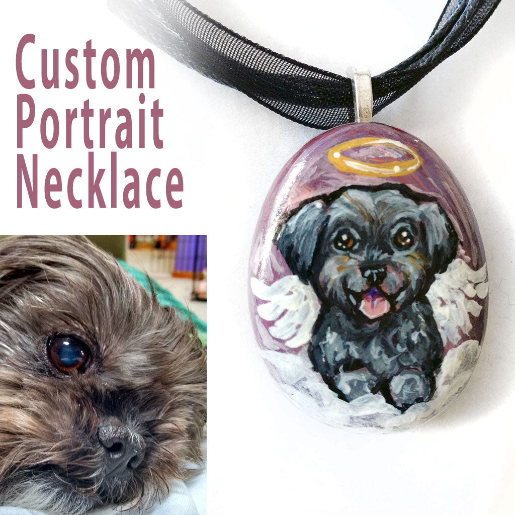 A custom dog portrait necklace, crafted from a small beach rock, includes art of a black and brown Affenpinscher