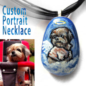 a custom pet portrait, painted on a small beach stone, of a brown dog as an angel and handmade into a neckalce