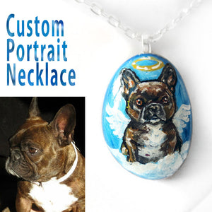 A beach pebble custom made into a pendant necklace, with the portrait of a brown French bulldog as an angel.