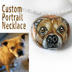 a peach coloured beach stone, painted with the a custom portrait of a Staffordshire Terrier dog and handmade into a necklace